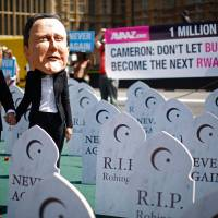 Burma advocates: Campaigners supporting the 'Avaaz, Burma Campaign UK' organization wear masks representing British Prime Minister David Cameron (right) and Myanmar's President Thein Sein as they pose for photographs during a Monday protest photo call outside the Houses of Parliament in London. | AP
