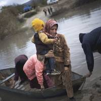 Crisis mode: Syrian refugees cross into Turkey via the Orontes River, near the village of Hacipasa, in December 2012. | AP