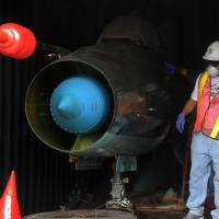 Disturbing discovery: A worker on Sunday guards a container in which one of two Soviet MiG-21 fighter planes were found aboard a North Korean-flagged ship seized this month at Manzanillo port in Colon, Panama. | AFP-JIJI