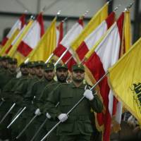 Red flags: Hezbollah fighters, holding up Lebanese flags and the yellow flag of the militant Shiite Muslim group, parade through the southern suburbs of Beirut in November 2009. | AFP-JIJI