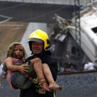 Survivor: A fireman carries an injured girl after Wednesday's high-speed derailment near Santiago de Compostela, Spain. | AFP-JIJI