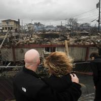 Family disaster: Robert Connolly embraces his wife, Laura, on Oct. 30 as they survey the remains of her parents' home, one of more than 50 houses that burned to the ground in the Breezy Point section of New York during Superstorm Sandy. | AP