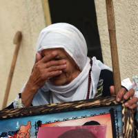 Peace process progress: The mother of a Palestinian held in an Israeli prison for 22 years holds a picture of her son at her home in the Shati refugee camp in Gaza City, Gaza Strip, on Sunday after hearing news of his possible release. | AFP-JIJI