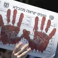 Unpersuaded: An Israeli protester holds a sign depicting bloody handprints and a Hebrew slogan reading 'prison release form' during a rally against the proposed release of Palestinian prisoners from Israeli jails in Jerusalem on Sunday. | AP