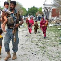 Consulate bombing: An Afghan policeman carries a boy at the site of a suicide attack in front of the Indian Consulate in Jalalabad on Saturday. | AFP-JIJI