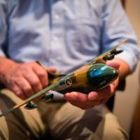 Retired U.S. Air Force Maj. Wes Carter holds a model of a C-123 cargo plane at his home in McMinnville, Oregon, last month. | THE WASHINGTON POST