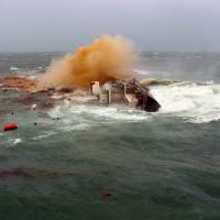 Doomed: The carrier Trans Summer tips onto its side off Hong Kong in rough seas whipped up Wednesday by Typhoon Utor. | AFP-JIJI