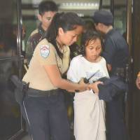 Shock: A survivor is helped as she arrives at a hospital early Saturday after the ferry she was aboard sank in a collision with a freighter off Cebu in the central Philippines. | AFP-JIJI