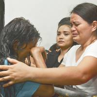 Grief: A survivor (left) of a ferry sinking cries as she arrives at a hospital in Cebu early Saturday. | AFP-JIJI