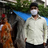 Questionable care: A cancer patient stands outside a temporary shelter located on the pavement outside Tata Memorial Hospital in Mumbai at the beginning of August. Some of the city's streets act as an unofficial ward for patients attending one of India's top cancer treatment centers. | AFP-JIJI