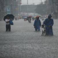 Our fault?: Residents wade through a street in Manila on Tuesday. A new U.N. draft report concludes there is a 95 percent certainty that human activity is responsible for most global warming. | AFP-JIJI