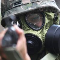 As good as dead: A South Korean soldier aims a machine gun in a military exercise with the U.S. in Seoul on Wednesday as a U.N. meeting in the city heard tales of North Korea's prison system. | AP