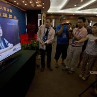 Taking the stand: Journalists watch online pre-recorded testimony given by Gu Kailai, wife of former Chinese politician Bo Xilai, before a news conference at a hotel near the Jinan Intermediate People's Court in Jinan, Shandong province, on Friday. | AP