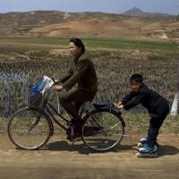 Slow going: A North Korean boy on Rollerblades is pulled by a woman on a bicycle near Kaesong, just over the border from South Korea, in April. | AP