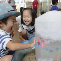 A boy touches a block of ice at Nakamura Station of the Tosa Kuroshio Railway in Shimanto, Kochi Prefecture, on Tuesday as the city became the first observation site in Japan to ever reach 40 degrees four days in a row, according to the Meteorological Agency. Story: Page 2. | KYODO