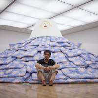 Work and play: Tsuyoshi Ozawa with a mountain of futons, which he created for kids in Fukushima. | KENJI AOKI