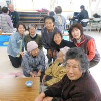 Making a difference: Kerry Shioya (middle row, second from right) poses with residents living in temporary housing units in Rikuzentakata, Iwate Prefecture, during a recent visit to the tsunami-devastated city. | COURTESY OF KERRY SHIOYA
