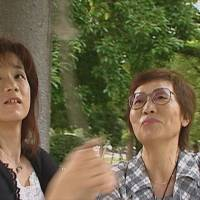 Emiko Okada (right) and her daughter, Yukie Tominaga, ring a Peace Bell in Hiroshima Peace Memorial Park in summer 2006. | COURTESY OF SMARTGIRL PRODUCTIONS LLC