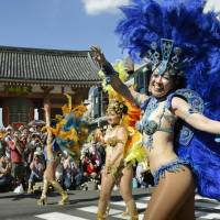 Carnival queens: Costumed revelers parade through the streets of Tokyo during a previous Asakusa Samba Carnival. | KYODO