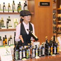 Goes with anything: An employee of olive oil speciality shop Olioteca in Shinjuku Ward, Tokyo, offers various oils imported from Italy for tasting before purchase in late June. | KYODO