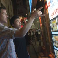 Buyer's market: An American tourist (left) looks at advertisements for residential properties displayed outside a real estate agency in Tokyo on July 6. | BLOOMBERG