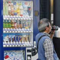 Ah, soda: A man drinks a Pepsi Nex soft drink developed by Suntory Beverage & Food Ltd. as he passes a vending machine in May. | BLOOMBERG