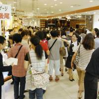 Hustle and bustle: Shoppers crowd the food floor at Kintetsu Department Store's flagship outlet in the Abeno Harukas building in Osaka on Monday. | KYODO
