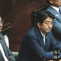 Down to business: Prime Minister Shinzo Abe and Justice Minister Sadakazu Tanigaki (left) attend a plenary session at the Lower House on Aug 2. | BLOOMBERG