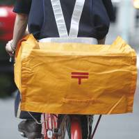 Special delivery: A Japan Post Co. mailman cycles on a street near one of the company's branches in Tokyo in mid-June. | BLOOMBERG