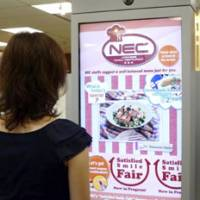 You want it: NEC Corp.'s PanelDirector, an electronic advertisement display panel that analyzes the preferences of a person standing in front of it, shows a mock pasta ad to a woman during a recent demonstration in Tokyo. | KYODO PHOTO
