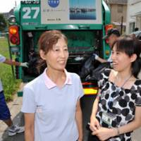 Not talking trash: Kuniko Fujita (center), leader of the Koto Eco Community Conference, and Satomi Nagate, a senior member of the LEAF nonprofit organization, speak in front of a garbage truck in Nishinomiya, Hyogo Prefecture. | KYODO PHOTO