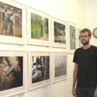 Preserving the present: Sam Seager stands by his exhibition of photographs of rural Japan at the Orange Dot Gallery in London on Sept. 16. | KYODO PHOTO