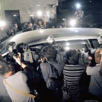 In the spotlight: Photographers surround a car carrying prosecutor Tsunehiko Maeda as he was driven to the Osaka Detention House on Sept. 21 after his arrest for allegedly falsifying investigative data. | KYODO PHOTO