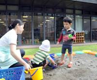 Child's play: A nursery teacher plays with children in the yard of Kid's Square Nagatacho, located in one of the office buildings for Diet members in Chiyoda Ward, Tokyo, on Sept. 29. | SATOKO KAWASAKI PHOTO