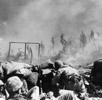 Fight of their lives: In this November 1943 file photo released by the U.S. Marine Corps, smoke is seen rising from the wreckage of Japanese defense installations as U.S. Marines crouch for cover in Tarawa, Gilbert Islands. | AP PHOTO