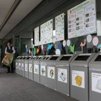 Keeping them honest: Volunteers at the COP10 biodiversity meeting keep track of the use of trash bins for separating garbage at the Nagoya Congress Center. | SETSUKO KAMIYA