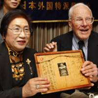 Long time coming: Franklin Hobbs, a former U.S. soldier who fought in the Battle of Iwojima, and Chie Takekawa, whose father was killed on the island, hold a framed letter and a photo of her sister at the Foreign Correspondents' Club of Japan in Tokyo on Friday. | AP PHOTO