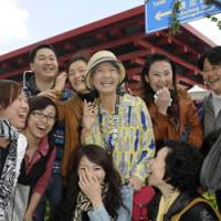 Expo explorer: Tomiyo Yamada (standing at center), the Japanese housewife dubbed 'The Lady of Shanghai Expo,' shares smiles with Chinese visitors Saturday as the six-month event neared its end. | KYODO PHOTO