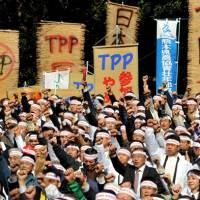 Fists of fury: Farmers at a rally Wednesday in Hibiya Park in central Tokyo show their opposition to the government starting talks on joining the Trans-Pacific Partnership free-trade pact. | YOSHIAKI MIURA PHOTO