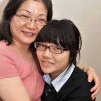 New lease: Mei Sano is hugged by her mother, Tomoko, after an interview at Nihon Kogyo Daigaku Komaba High School in Tokyo on Oct. 21. Sano underwent a heart transplant operation last year in New York. | YOSHIAKI MIURA PHOTO