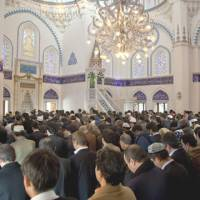 Keeping the faith: Muslims worship in the prayer hall of the Tokyo Camii & Turkish Cultural Center in Shibuya Ward. Tokyo Camii is Japan's second-oldest mosque, having been originally built in 1938. | COURTESY OF TOKYO CAMII & TURKISH CULTURAL CENTER