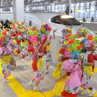 Finish line: Dancers from the famed Aomori Nebuta Festival welcome the first bullet train to arrive at Shin-Aomori Station in Aomori Prefecture, from Morioka, Iwate Prefecture, on Saturday morning. | KYODO PHOTO
