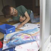 Body and soul: Takenobu Yanagita paints at Maru studio in the city of Fukuoka on June 14. | KYODO
