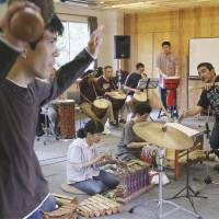 Jamming: Shin Fukumori (right), head of the Shobu Gakuen rehabilitation facility for the mentally disabled in the city of Kagoshima, leads a percussion group rehearsal June 3. | KYODO
