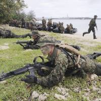 Bilateral bonds: Ground Self-Defense Force troops train with the U.S. Marines on Guam last September to 'recapture' an isolated island that's hypothetically fallen into enemy hands. | KYODO