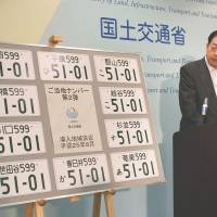 Stamped: Transport minister Akihiro Ota introduces license plates bearing 10 of the new issuing offices at a Friday press conference in Tokyo. | KYODO