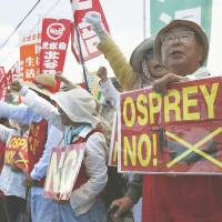 Speaking up: Residents stage a rally Saturday morning at one of the gates for the Futenma airbase in Okinawa Prefecture to protest the arrival of more Osprey aircraft. | KYODO