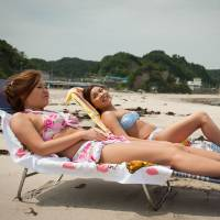 Worrisome undercurrents: Masumi Shiota, 22, and Izumi Seya, 21, relax on Nakoso Beach near Iwaki, Fukushima Prefecture, on July 22. | THE WASHINGTON POST