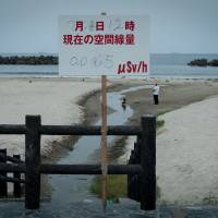 Reminder: A sign lists the radiation level of the sand at Nakoso Beach near Iwaki on July 22. | THE WASHINGTON POST