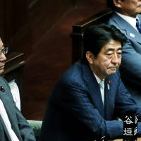 Listening: Prime Minister Shinzo Abe attends a Diet session in the Lower House on Friday while Justice Minister Sadakazu Tanigaki looks on. | BLOOMBERG